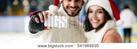 Panoramic Shot Of Smiling Couple In Santa Hats Taking Selfie On Smartphone On Skating Rink At Christ