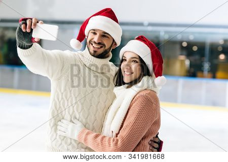 Smiling Couple In Santa Hats Taking Selfie On Smartphone On Skating Rink At Christmastime