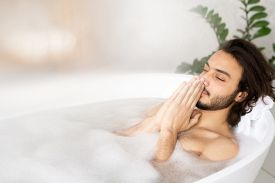 Young serene man meditating while enjoying hot bath with foam with his hands put together by face