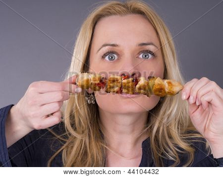 Hungry woman smelling grilled meat poster