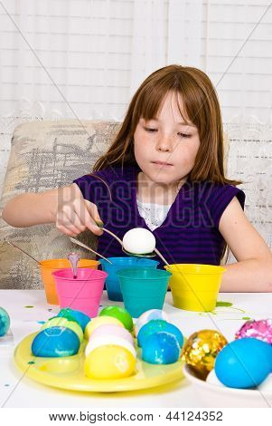 Young girl coloring Easter Eggs