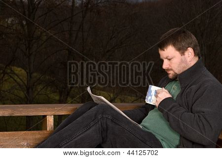 Young man with coffee cup and newspaper