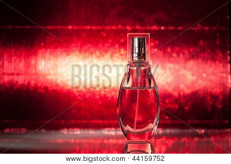 Bottle of perfume on red background