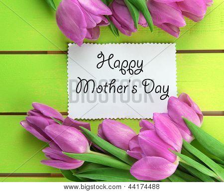 Lindo buquê de tulipas roxas e placa de fundo verde de madeira