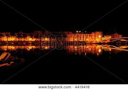 Mediterranean Town Along River Bank At Night.