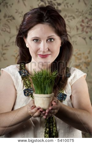 Woman With Small Pot Of Green Grass