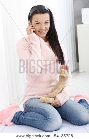 Smiling young woman sitting between heels on floor at home, talking on mobile phone, holding soft toy in hand.