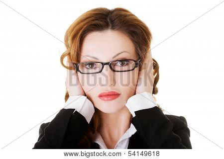 Attractive business woman with covered ears. Isolated on white.