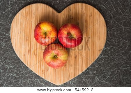 Three Red Apples On Heart Shaped Chopping Board