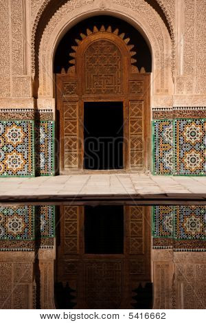 Ancient Moroccan Door And Mosaic Reflected In Outdoor Pool