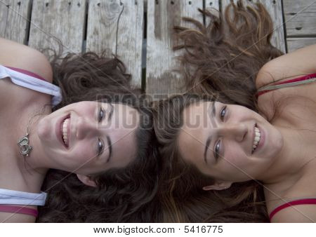 Two Teenage Girls Lying On Dock, Head To Head