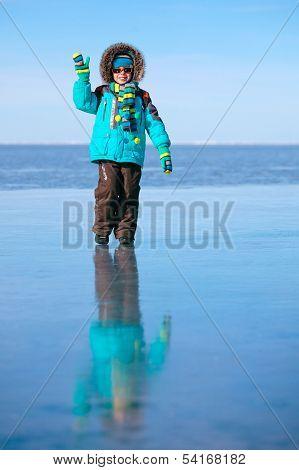 Cute little boy outdoors standing on frozen sea