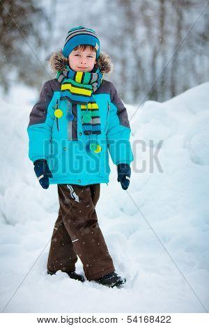 Portrait of cute little boy in winter clothes