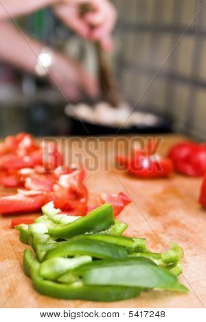 Chopped Red And Green Pepper On A Wooden Board