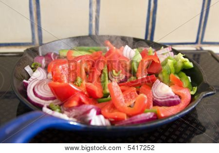 Peppers And Onions Cooking In A Pan On An Electric Hob