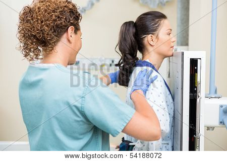 Rear view of female nurse preparing patient for chest xray in examination room