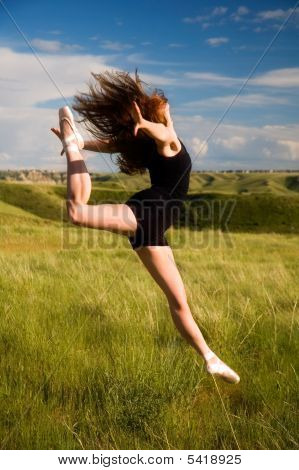 Ballerina Jumping In A Field