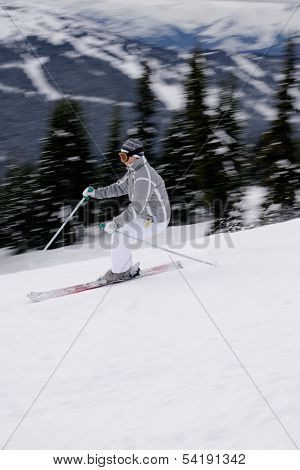 A Young Female Skier Enjoying Downhill Skiing In British Columbia Mountains