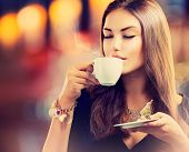Coffee. Beautiful Girl Drinking Tea or Coffee in Cafe. Beauty Model Woman with the Cup of Hot Beverage. Warm Colors Toned poster