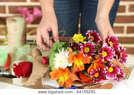 Female hands composing beautiful bouquet, close-up. Florist at work. Conceptual photo