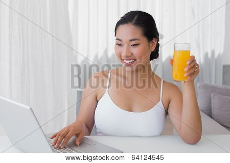 Happy woman using laptop and having orange juice at home in the living room