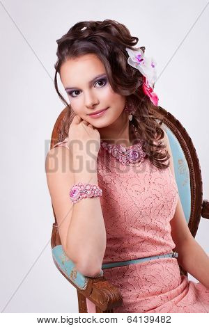 Pretty Woman In A Pink Dress With Flowers In Her Hair Smiling