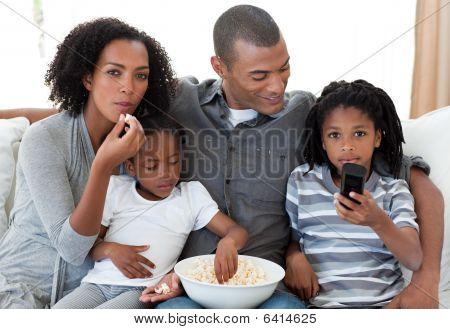 Familia afroamericana viendo una película en casa