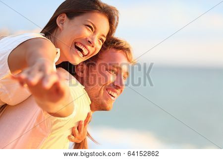 Beach couple laughing in love romance on travel honeymoon vacation summer holidays romance. Young happy people, Asian woman and Caucasian man embracing outdoors on tropical beach in casual wear.