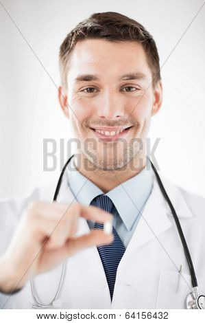 healthcare and medical concept - young male doctor offering pill