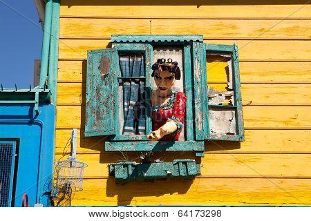 LA BOCA, BUENOS AIRES - MAR 15 2014 :  A figure beckons at a window in the Caminito area of La Boca