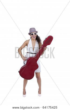 Happy young woman wearing sunglasses posing with guitar