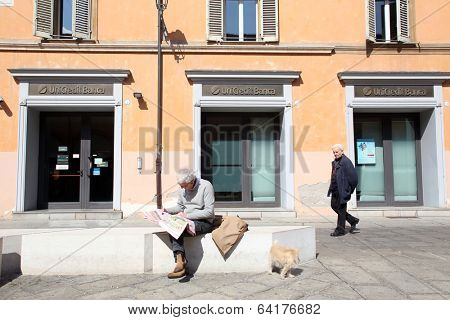 BOLOGNA, ITALY - APRIL 19, 2014: A man walks past a  Unicredit Banca di Roma S.p.A bank office in Bologna, Italy, on Saturday, April 19, 2014.