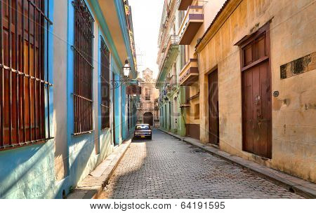 HAVANA, CUBA-MAY 14: Street scene with an old rusty american car on May 14, 2013 in Havana.These vintage cars that can be seen all over the country have become a worldwide known symbol of Cuba