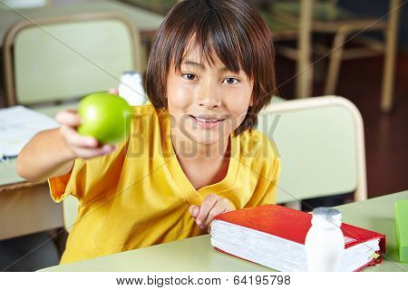 Child in elementary school showing healty lunch with apple and milk
