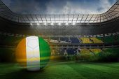 Football in ivory Coast colours against large football stadium with brasilian fans poster