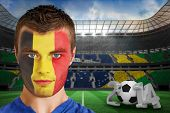 Composite image of serious young belgium fan with face paint against large football stadium with brasilian fans poster