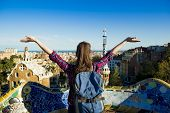 Rear view of young female tourist enjoying the view in Parc Guell in Barcelona, Spain. poster