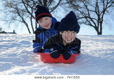 Two Young Boys Sledding Downhill Together