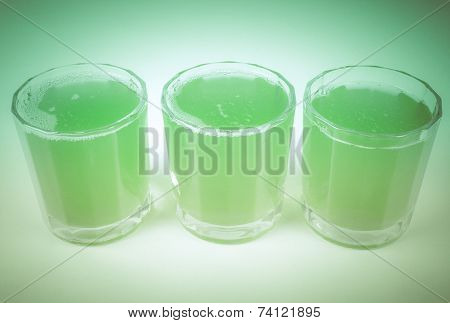 Vintage looking Glasses of green apple juice on continental breakfast table poster