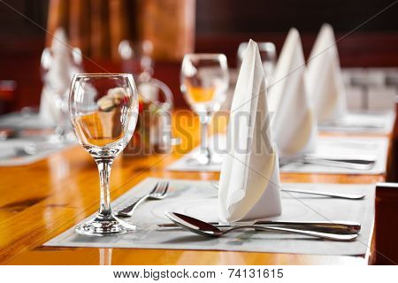 Glasses and plates on table in restaurant - food background