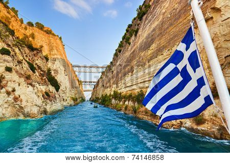 Corinth channel in Greece and greek flag on ship - travel background