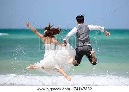 Happy Just Married Young Couple Celebrating And Have Fun At Beach Sunset