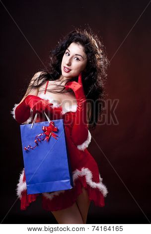 Sexy santa helper. Red dress and gloves. Carrying bag with gifts