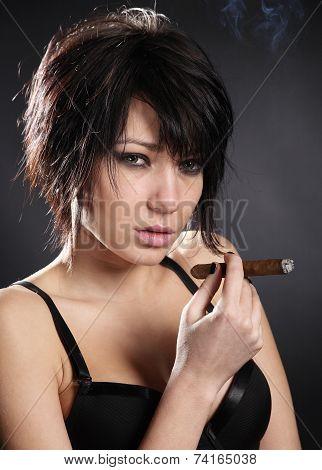 Sexy brunette woman with black bra smoking cigar
