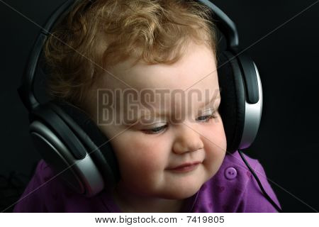 Baby listening to music with huge headphones on black background