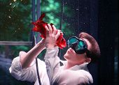 Young man kissing fish underwater poster
