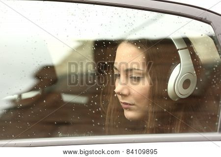 Sad Teenager Girl In A Car With Headphones