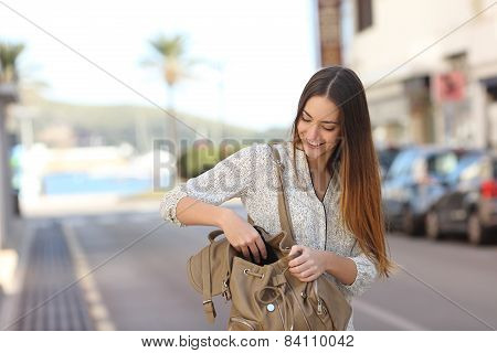 Woman Walking On The Street And Searching In A Bag