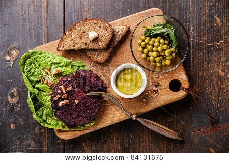 Beet Cutlet Vegan Meatless Served With Green Peas Salad On Dark Wooden Background