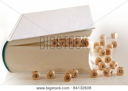 story - message for creativ writing spelled with wooden letter blocks between pages of a white book several blurry letter blocks around poster
